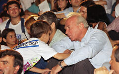 A child shakes the hand of Yitzhak Rabin, head of the Labor party, at an election rally held June 20, 1992 in Tel Aviv, days before Rabin's election victory. (AP Photo/Nati Harnik)