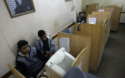 Illustrative: Palestinian men use a computer in the southern Gaza Strip on January 20, 2012. (Abed Rahim Khatib / Flash90)