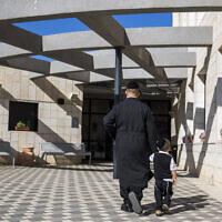 Illustrative: An ultra-Orthodox man walks his son to the Poalei Menahem Talmud Torah school, in the West Bank settlement of Beitar Illit,  September 4, 2016. (Nati Shohat/Flash90)
