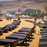 Empty sun loungers on a beach near the Dead Sea hotel complex, on July 10, 2019. (Gershon Elinson/Flash90)