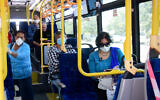 Commuters wear face masks as they ride a public bus in the southern city of Ashkelon, March 29, 2020 (Flash90)