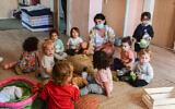 Children at a kindergarten in Tel Aviv return from a two month coronavirus lockdown on May 10, 2020. (Avshalom Sassoni/Flash90)