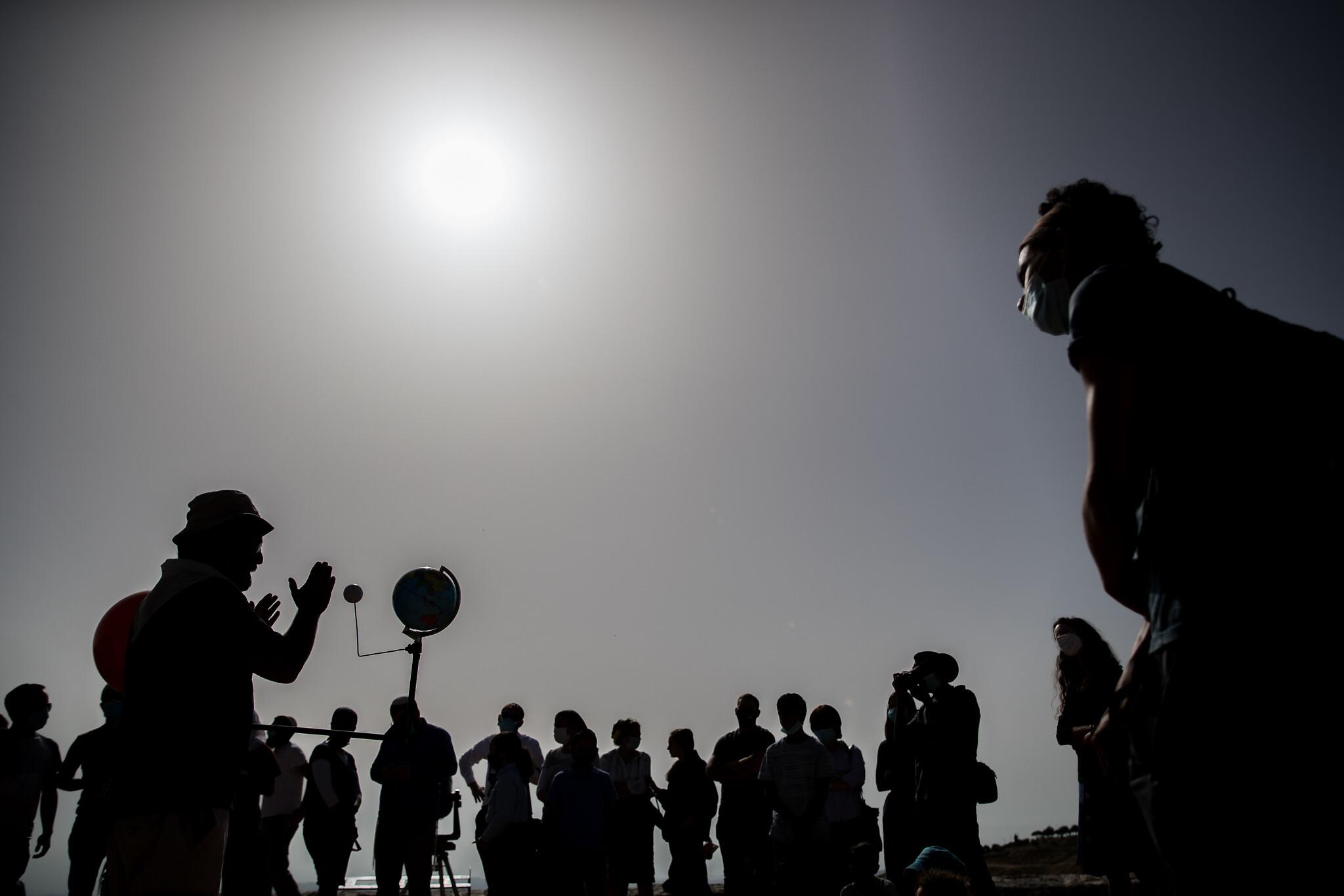 People observe a partial solar eclipse at Mount Scopus in Jerusalem on June 21, 2020. (Yonatan Sindel/Flash90)