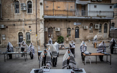 Ultra-Orthodox Jews from the Karlin (Hasidic dynasty) praying according to the social distancing rules outside their synagogue in Jerusalem on August 10, 2020 )Yonatan Sindel/Flash90(