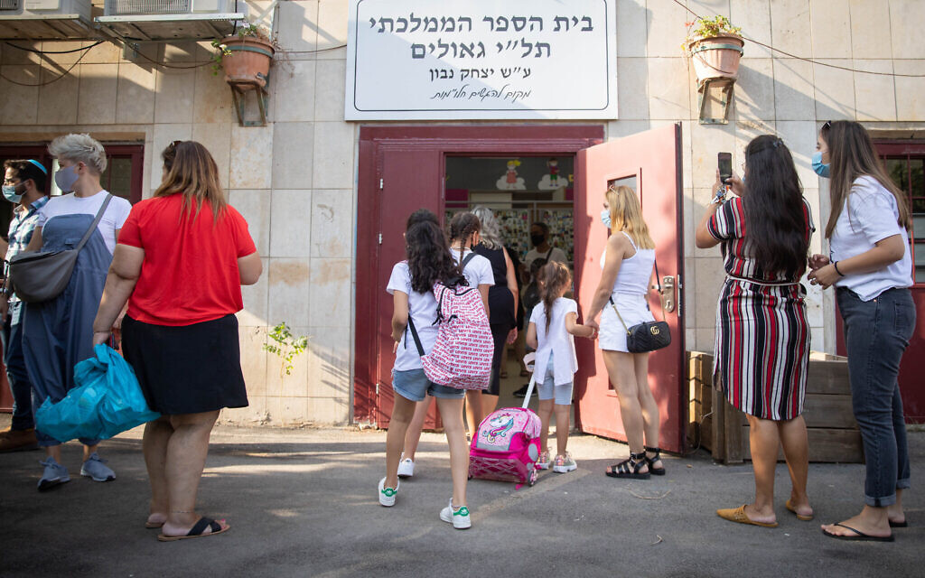 First grade students arrive for their first day of school at Tali Geulim school in Jerusalem on September 1, 2020. (Noam Revkin Fenton/Flash90)