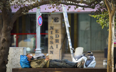 A man sleeps on a public bench next to closed shops on Hillel Street in downtown Jerusalem, on September 23, 2020, during a nationwide lockdown. (Nati Shohat/Flash90)