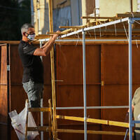 Jews build a sukka for the upcoming holiday of Sukkot, in the northern city of Safed, September 29, 2020. (David Cohen/Flash90)