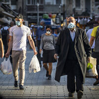 People wear face masks at the Mahane Yehuda market in Jerusalem on September 30, 2020, during a nationwide lockdown to prevent the spread of COVID-19. (Olivier Fitoussi/Flash90)