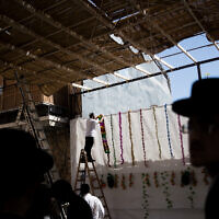 Men hang decorations in a newly built sukkah in the ultra-Orthodox neighborhood of Mea Shearim in Jerusalem on October 2, 2020 (Nati Shohat/Flash90)