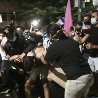 Police officers remove a protestor during protests against Prime Minister Benjamin Netanyahu at Habima Square in Tel Aviv on October 3, 2020. (Miriam Alster/Flash90)