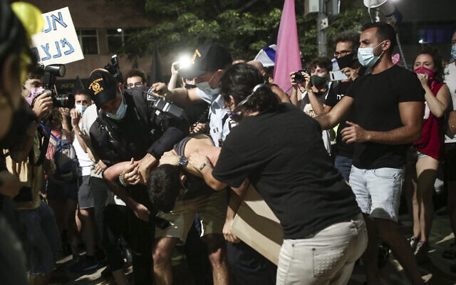 Police officers remove a protestor during protests against Prime Minister Benjamin Netanyahu at Habima Square in Tel Aviv on October 03, 2020. (Miriam Alster/Flash90)