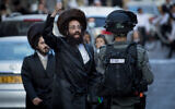 Police officers clash with Haredi men during a protest against the enforcement of coronavirus restrictions in the Jerusalem neighborhood of Mea Shearim, October 4, 2020. (Nati Shohat/Flash90)
