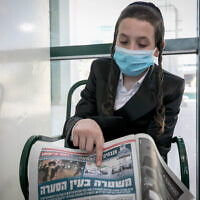 A boy who was seen on video getting hit by a bucket hurled by a cop in Beitar Illit a day earlier points to a copy of Israel Hayom with a picture of the incident, while in Jerusalem on October 5, 2020. (Olivier Fitoussi/Flash90)