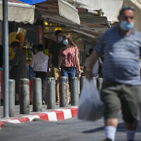 People wearing face masks shop at the Mahane Yehuda Market in Jerusalem on October 5, 2020, during a nationwide lockdown to prevent the spread of COVID-19. (Olivier Fitoussi/Flash90)