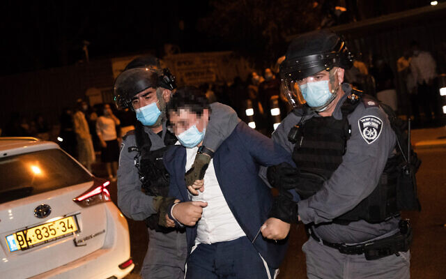Police officers arrest a protester during a rally against enforcement of coronavirus emergency regulations, outside the ultra-Orthodox Jewish neighborhood of Mea Shearim, in Jerusalem, October 5, 2020. (Yonatan Sindel/Flash90)