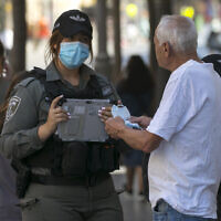 Border Police officers give a face mask to a man on Jaffa Street in downtown Jerusalem on October 7, 2020, during the nationwide coronavirus lockdown. (Nati Shohat/Flash90)