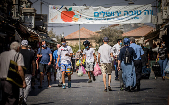 People wearing face masks shop at the Mahane Yehuda Market in Jerusalem on October 7, 2020, during a nationwide lockdown to prevent the spread of COVID-19 (Yonatan Sindel/Flash90)