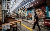 People wearing face masks walk through the largely shuttered Mahane Yehuda Market in Jerusalem on October 7, 2020, (Yonatan Sindel/Flash90)