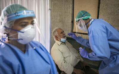 Health care doctors and medics take test samples of Jerusalemites to check if they have been infected with the coronavirus in Sheikh Jarrah, Jerusalem on October 08, 2020. (Olivier Fitoussi/Flash90)