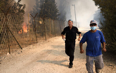 Men escape fire in Bat Hefer on October 9, 2020 (Gili Yaari/Flash90)