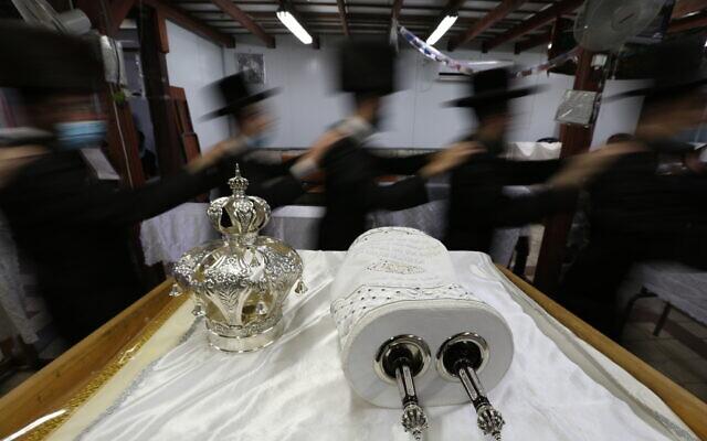 Illustrative: Ultra-Orthodox Jews dance during Simchat Torah celebrations, October 10, 2020 (David Cohen/Flash90)