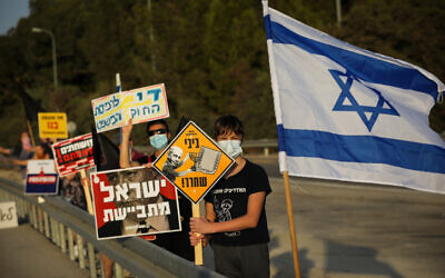 Activists protest against Prime Minister Benjamin Netanyahu on Route 3, in central Israel, October 10, 2020 (Nati Shohat/Flash90)
