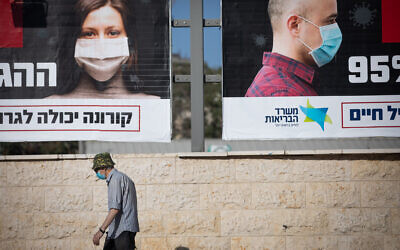 People walk past a billboard posted by the Health Ministry instructing people to wear face masks, in Jerusalem on October 11, 2020. (Yonatan Sindel/Flash90)