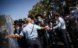 Police guard as ultra-Orthodox Jews attend the funeral of Rabbi Yechezkel Koren in the Bayit VeGan neighborhood of Jerusalem on October 12, 2020. (Yonatan Sindel/Flash90)