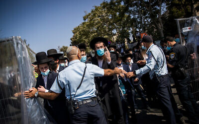 Police guard as ultra-Orthodox Jews attend the funeral of Rabbi Yechezkel Koren in the Bayit VeGan neighborhood of Jerusalem on October 12, 2020. (Yonatan Sindel/Flash90)