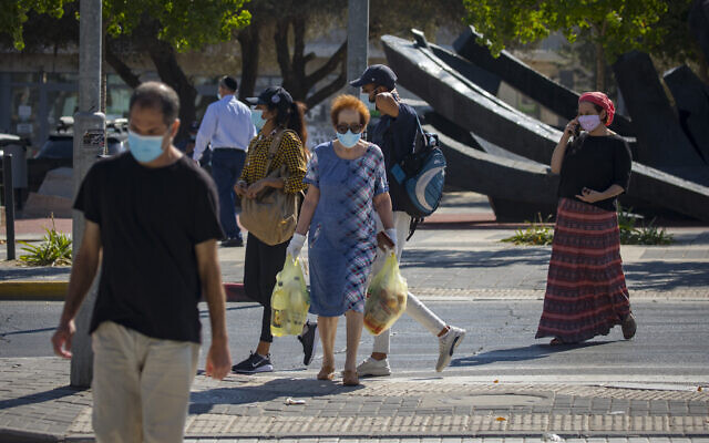 People wearing face masks walk in the Beit Hakerem neighborhood in Jerusalem on October 14, 2020, during a nationwide lockdown to prevent the spread of COVID-19 (Olivier Fitoussi/Flash90)