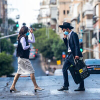 Ultra-Orthodox Jews walk in Bnei Brak on October 14, 2020, during a nationwide lockdown to prevent the spread of COVID-19. (Yossi Aloni/Flash90)