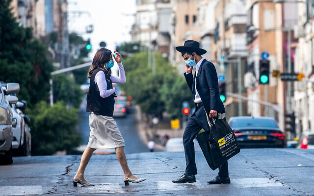Illustrative: Ultra-Orthodox Jews walk in Bnei Brak on October 14, 2020, during a nationwide lockdown to prevent the spread of COVID-19. (Yossi Aloni/Flash90)