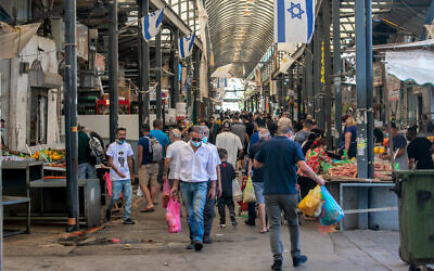 People shop at the open-air market in the central city of Ramle on October 16, 2020. (Yossi Aloni/Flash90)