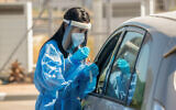 Illustrative: Clalit Health care workers take test samples for coronavirus at a drive-through site in Lod, on October 16, 2020. (Yossi Aloni/Flash90)