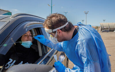 Clalit Health Services workers take swab samples for preschool and daycare staff members at a drive-thru coronavirus testing site in the central city of Lod, October 16, 2020. (Yossi Aloni/Flash90)