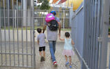 Parents accompany their children to kindergarten in Tel Aviv, on October 18, 2020. (Avshalom Sassoni/Flash90)