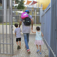 Parents accompany their children to kindergarten in Tel Aviv on October18, 2020. (Avshalom Sassoni/Flash90)