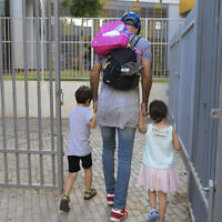 Parents accompany their children to the kindergarten in Tel Aviv as they return to kindergarten on October18, 2020, after being shut down during a national lockdown to prevent the spread of the Coronavirus. (Avshalom Sassoni/Flash90)