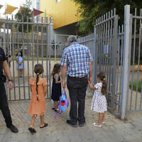 Parents accompany their children to the kindergarten in Tel Aviv as they return after a national lockdown was eased, October18, 2020 (Avshalom Sassoni/Flash90)