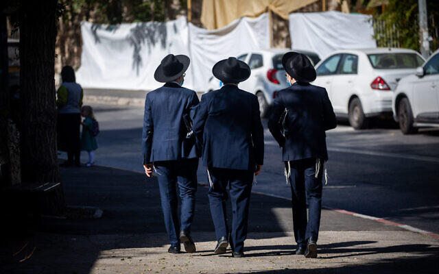 Ultra-Orthodox men walk in the Sanhedria neighborhood in Jerusalem on October 18, 2020. (Yonatan Sindel/Flash90)