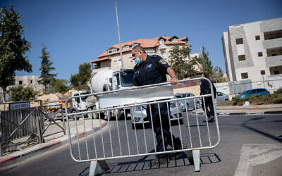 Police guard at a temporary checkpoint in the entrance to the neighborhood of Ramat Shlomo in Jerusalem in order to prevent the spread of the coronavirus on October 18, 2020. (Yonatan Sindel/Flash90)