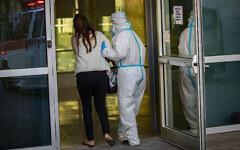 A Magen David Adom paramedic wearing protective equipment escorts a patient to the coronavirus unit at Hadassah Hospital Ein Karem in Jerusalem on October 19, 2020. (Olivier Fitoussi/Flash90)