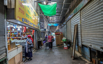 People walk in the almost empty market in Rehovot, on October 19, 2020 (Yossi Aloni/Flash90)