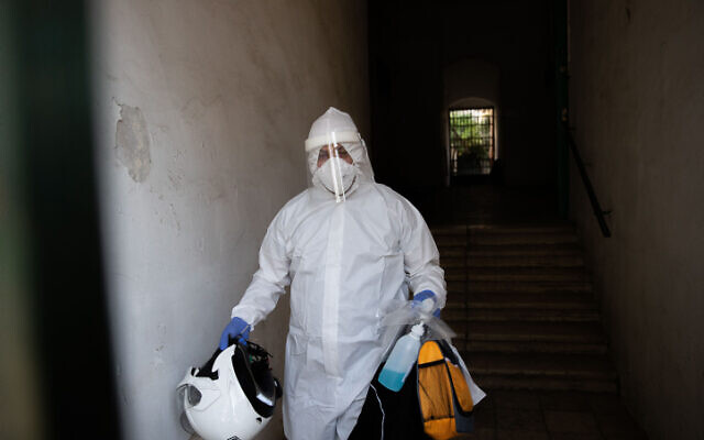 A United Hatzalah medical worker wears protective clothing as a preventive measure against the coronavirus, leaving after testing a patient with symptoms of COVID-19 in Jerusalem on October 19, 2020.  (Yonatan Sindel/Flash90)