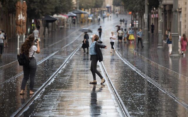 People cavort in the rain on Jaffa street in Jerusalem on October 20, 2020. (Nati Shohat/Flash90)