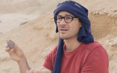 Dr. Filipe Natalio, seen here at a site in the Negev Desert, holding a flint tool. (screenshot)