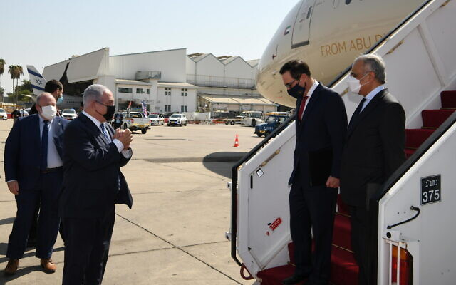 PM Netanyahu, left, greets US Secretary of the Treasury Steven Mnuchin and UAE Minister of State for Financial Affairs Obaid Humaid Al Tayer ahead of a ceremony during which Israel and the UAE signed four bilateral agreements at Tel Aviv's Ben Gurion Airport, October 20, 2020 (Amos Ben Gershom/GPO)