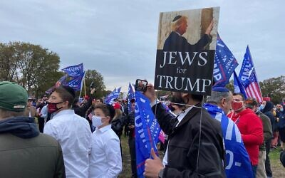 People gather near the stage of a pro-Trump rally at Marine Park in Brooklyn, New York on October 25, 2020. (Jacob Magid/Times of Israel)