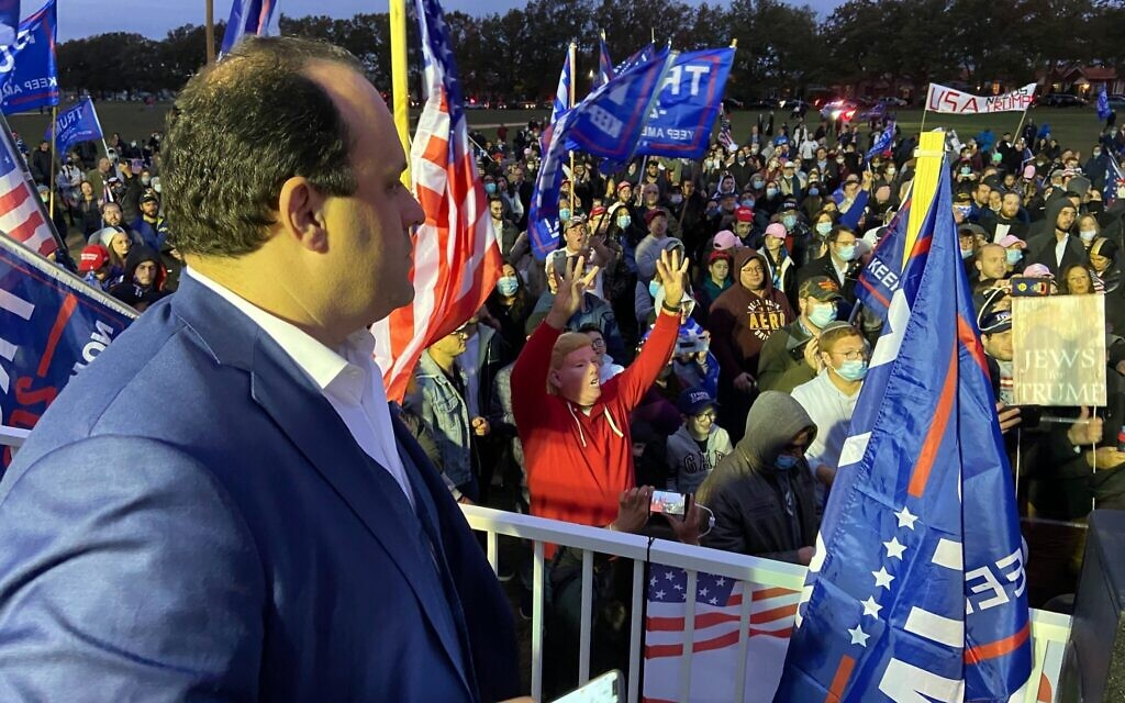 Trump campaign Jewish outreach director Boris Epshteyn (L) looks on  while onstage at a pro-Trump rally in Marine Park Brooklyn on October 25, 2020. (Jacob Magid/Times of Israel)