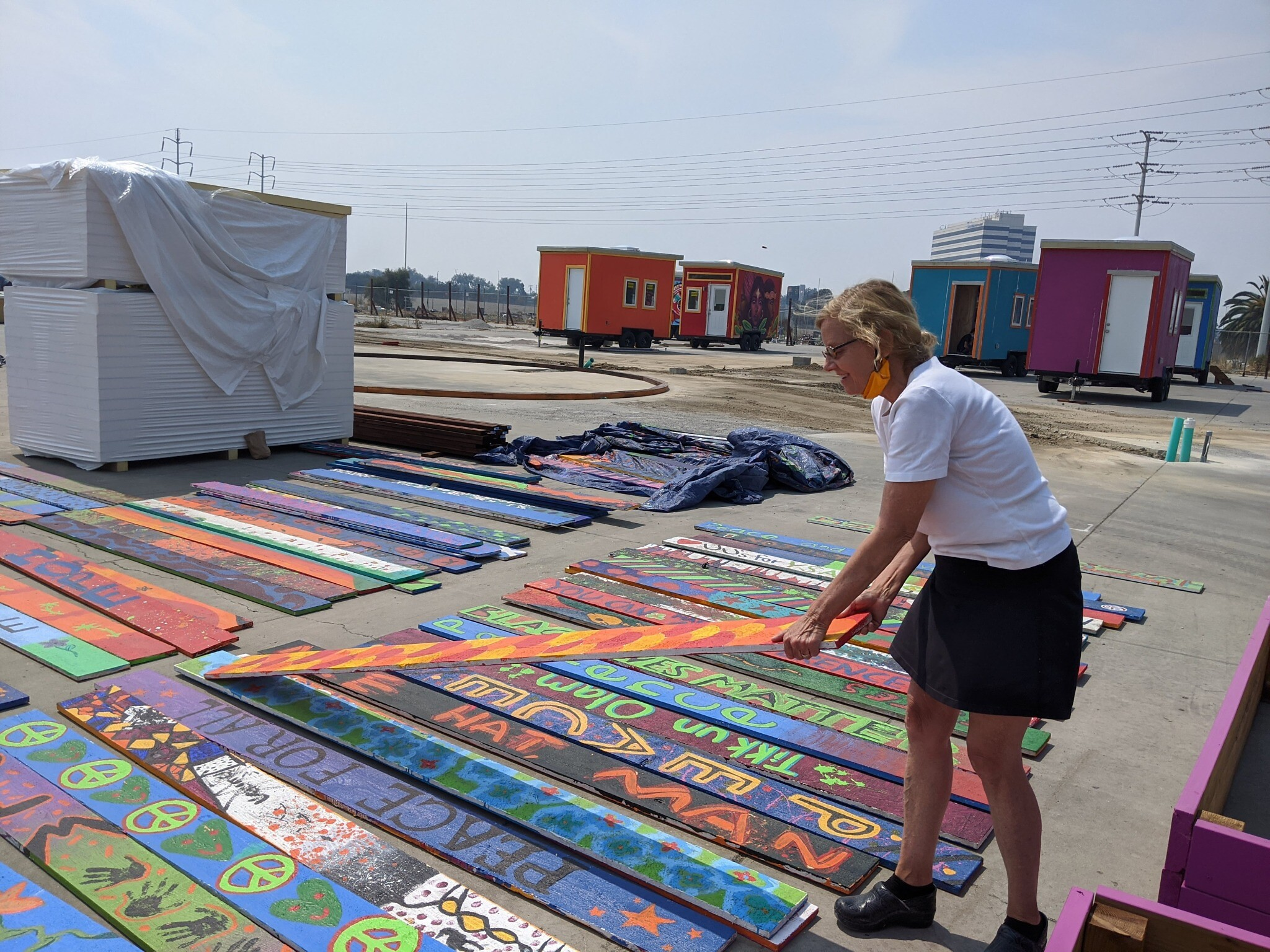 Sally Hindman, Youth Spirit Artworks founder and director, arranges some of the prayer and blessing planks for the perimeter fence at the YSA Tiny House Village in Oakland, California on September 20, 2020. (Melanie Lidman/Times of Israel)